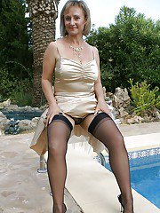 Big titted mature spreading her legs and rubs her huge melons at the pool