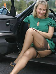 Mature lady in stockings pulls up her skirt and shows her pussy in the car