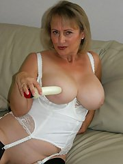 Mature fatty in black stockings and white lingerie playing with a dildo