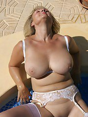Mature blond in white lingerie and stockings posing and masturbating in the pool