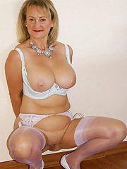 Seductive blonde mature vixen reveals her chubby body and her big jugs in sexy white