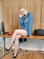 Strict MILF in glasses and stockings revealing her plump beauty in the office