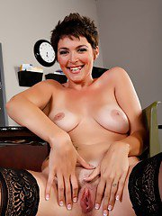 Lusty short haired MILF babe Charlie James posing in black stockings.