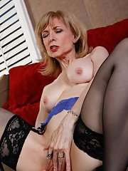 Raunchy mom Nina Hartley posing in gartered stockings and blue lingerie