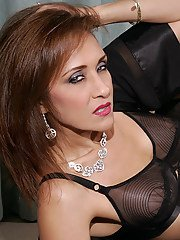 Mature redhead Roni showing off in black lingerie and stockings