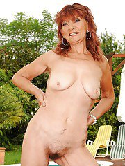 Mature lady is stripping by the pool outdoor to show her body