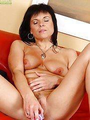 Busty mature babe Linette taking off her lingerie and toying her pink hole