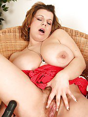 Fatty MILF with huge jugs masturbating her bush with a big black dildo