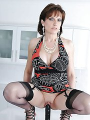 Busty mature lady in stockings sucks and rides a big black toy