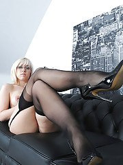 Busty blonde babe in glasses posing in stockings on the sofa