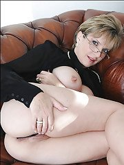 Sexy mature babe in glasses uncovering her huge tits and pussy