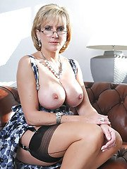 Tempting mature babe in fancy dress exposing her tits and teasing her vag