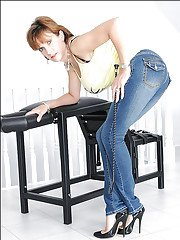 Voluptuous mature lady on high heels posing in skin-tight jeans
