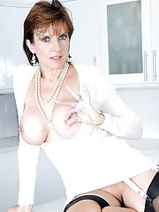 Busty mature lady in stockings spreading her legs and exposing her slit