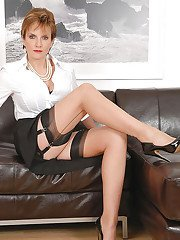 Sexy mature babe in stockings posing on the sofa and spreading her legs