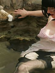 Seductive mature lady in glasses posing in the pool in her clothes