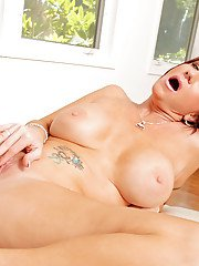 Sexy MILF Brittany Blaze stripping off her clothes and fingering her pussy