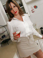Seductive mature babe drinking beer and stripping in the kitchen