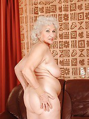 Lusty granny with huge tits stripping off all of her clothes