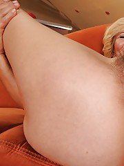 Horny granny on high heels stripping and fingering her hairy slit