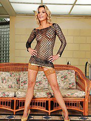 MILF babe in a fishnet dress strips to get a closeup of her cunt