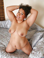 Buxom ebony babe with big tits posing on the bed and spreading her legs
