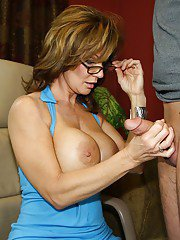 Lusty mature lady in glasses gets a cumshot on her big tits after handjob