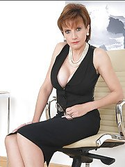 Mature babe with big tits posing in black dress with low decollete