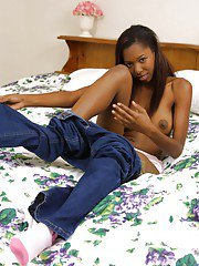 Graceful ebony chick with long legs Kandi Kane stripping on the bed