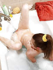 Skinny teenage cutie fingering her shaved pink hole in the bath