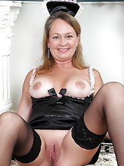 Naughty mature maid uncovering her boobs and toying her cunt