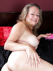 Big busted mature lady in glasses stripping and spreading her legs