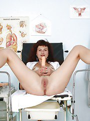 Mature lady stuffing her pink vag with a vibrator and gyno tools