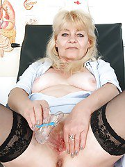 Salacious mature lady in nurse uniform playing with her sex toys