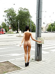 Kinky brunette amateur with long legs posing naked in the public place