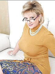 Mature lady in glasses uncovering her big jugs and shaved cunt