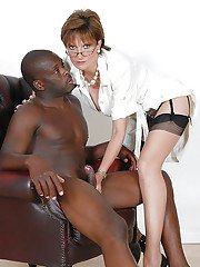 Big busted mature lady in glasses gives a handjob to a black guy
