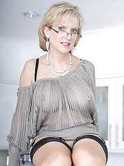 Bottomless mature lady in a sheer blouse exposing her shaved vag