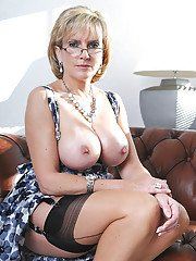 Wooing mature blonde in glasses revealing her enhanced jugs and juicy cunt