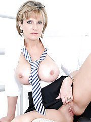 Salacious mature blonde in formal suit reveals her big jugs and cunt