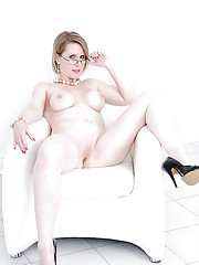 Busty mature lady in glasses slipping off her lacy lingerie