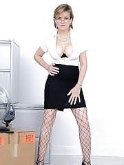 Mature lady in formal suit and fishnet pantyhose revealing her round jugs