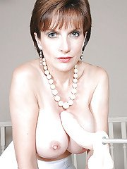 Barely clothed mature vixen in stockings has some fun with a dildo