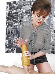 Lewd mature fetish lady pleasing a hard dick with her hands and flashlight
