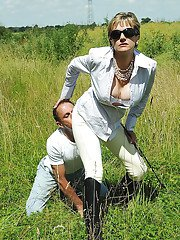 Mature femdom in sunglasses has some fully clothed fun outdoor
