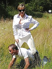 Fully clothed mature femdom in sunglasses abuses her male pet outdoor
