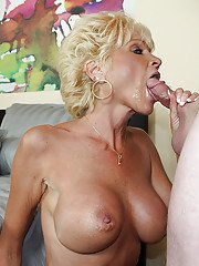 Salacious mature blonde with big jugs gives a blowjob to a younger lad