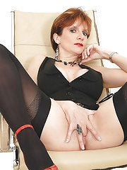 Bottomless mature gal in stockings fingering her trimmed pussy