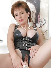 Horny mature lady in fetish outfit gets her pussy pleased with a machine