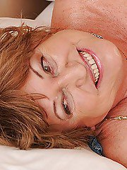 Fatty granny with massive flabby jugs taking off her lingerie on the bed